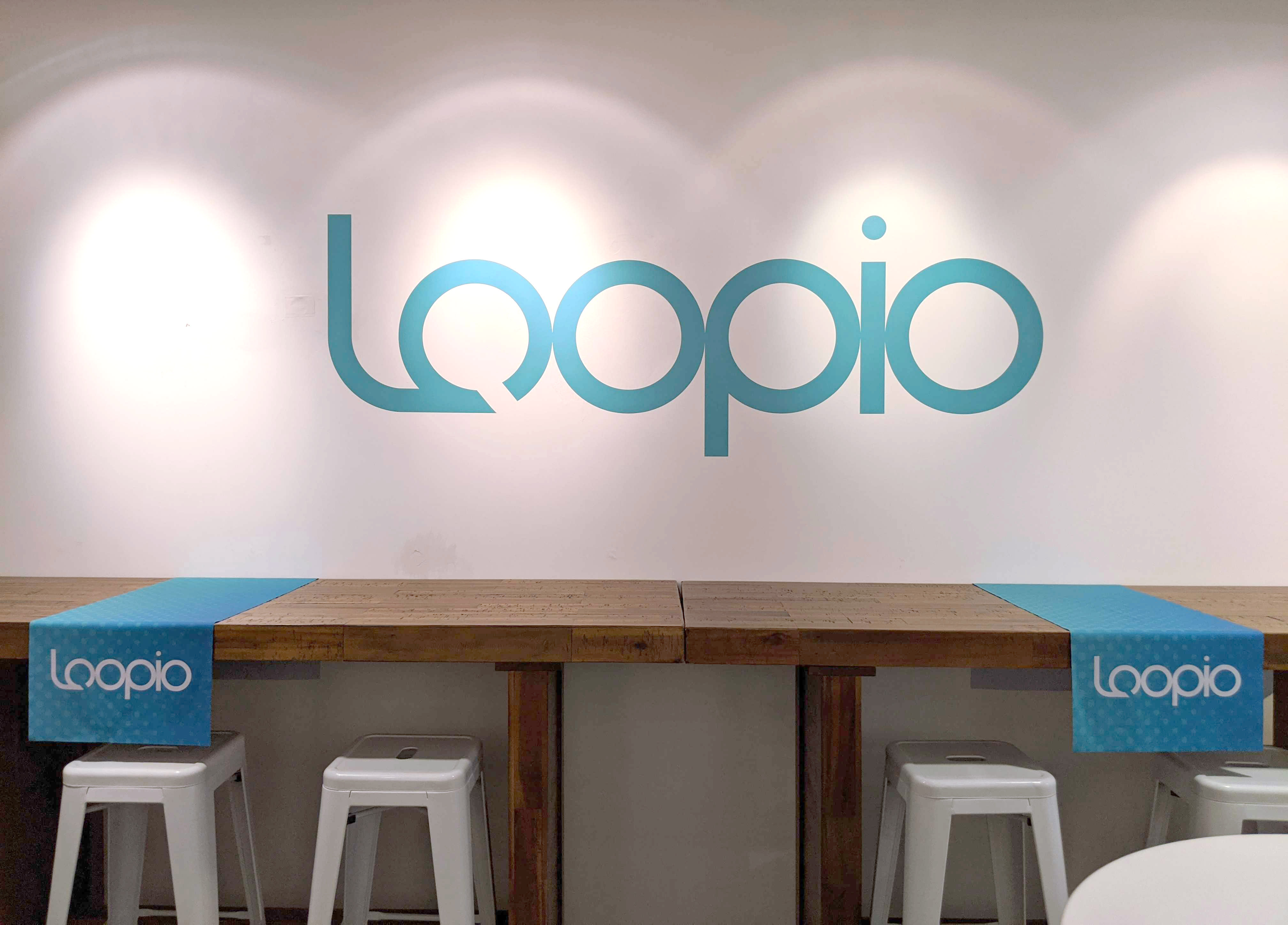 White wall with teal vinyl cling of Loopio logo