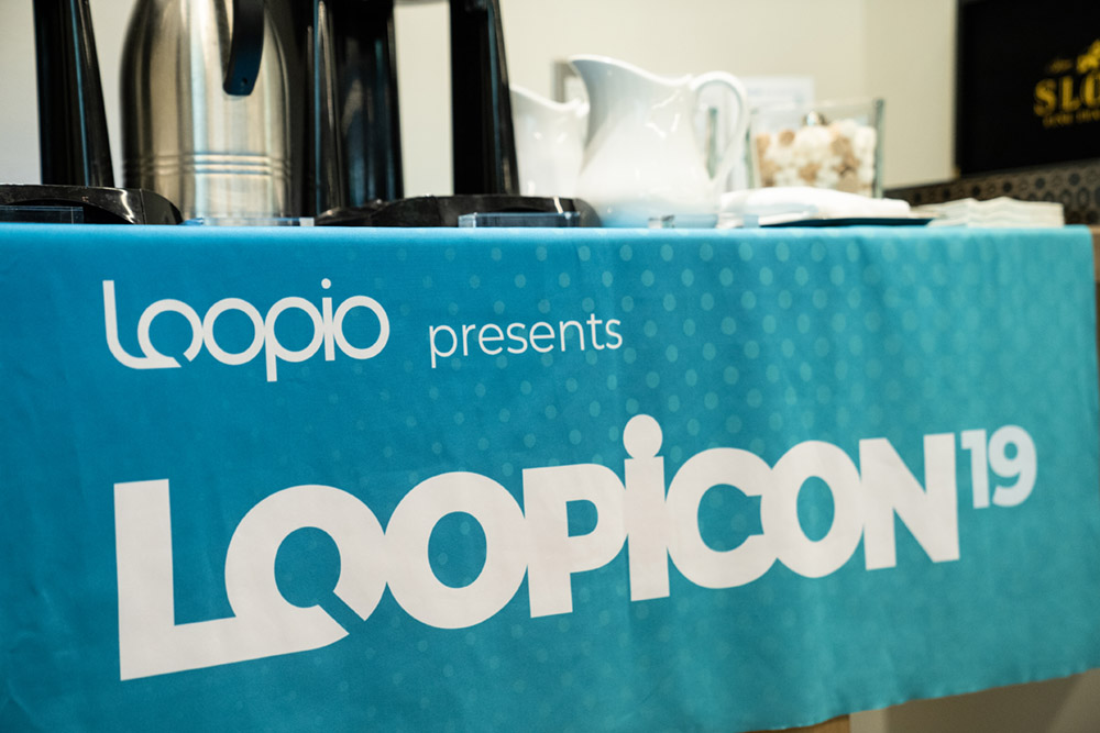 A hanging tablecloth with the logo with some coffee posts and creamer in the background